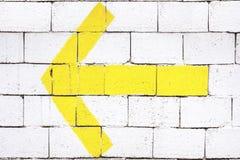 A yellow arrow on a brick wall Stock Image