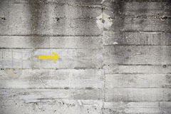 Yellow arrow on cement wall. Yellow arrow cement wall, detail of a dirty concrete wall with an arrow indication Stock Photo