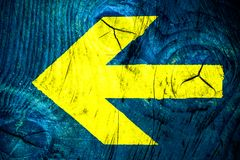 Yellow arrow direction sign over vivid bright blue color wooden wall with imperfections and cracks in a simple background texture. Space. Photo color toned royalty free stock photos