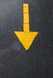 Yellow arrow down on asphalt street Stock Photos