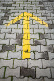 Yellow arrow on gray cobblestone pavement Royalty Free Stock Image