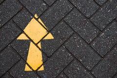 Yellow arrow paint on black brick concrete Stock Image