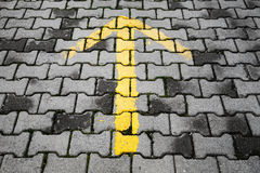 Yellow arrow painted on dark gray cobblestone pavement Royalty Free Stock Image