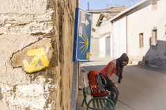 Yellow arrow painted on a stone made wall and a pilgrim woman on the way to Santiago Royalty Free Stock Images