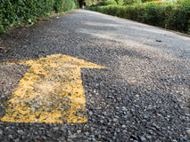 Yellow arrow on park runway Stock Images