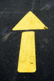 Yellow arrow on pavement Stock Images