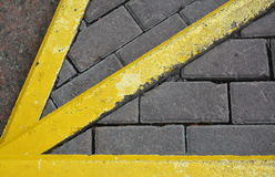 Yellow arrow pointer to the pavement. Street marking. Pavement marking. Grunge yellow lines Stock Photos