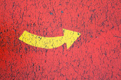Yellow arrow in the red background. Red asphalt and the yellow arrow - especcially for the children Royalty Free Stock Images
