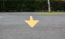 Yellow arrow sign from backward to front on parking lot. Single arrow sign from backward to front on parking lot Stock Photography