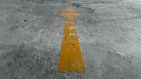 Yellow Arrow Sign On The Ground Stock Photo