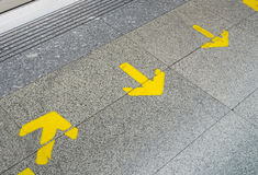Yellow arrow sign indicate on marble floor Stock Images