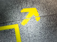 Yellow arrow sign indicate on marble floor Stock Image