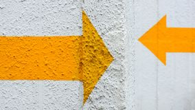 Yellow arrow sign painted. On white concrete wall Stock Photos