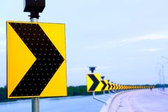 Continuous arrow sign on the curve. Yellow arrow sign reflects the light on the curve and the background has a blurred image of the arrow sign royalty free stock images