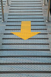 Yellow arrow sign on walkway Royalty Free Stock Photo