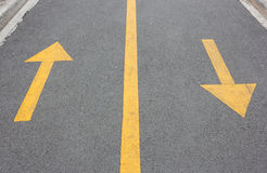 Yellow arrow up and down on asphalt street Stock Photos