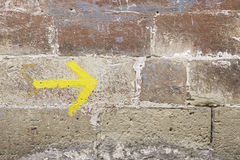 Yellow arrow on a wall Royalty Free Stock Photo