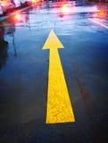 Yellow Arrow. Wet bright yellow arrow in carpark stock photo