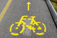Yellow arrows and bicycle sign of a cycling path Stock Photo