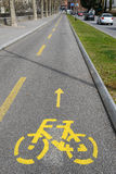 Yellow arrows and bicycle sign of a cycling path Stock Photos