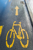 Yellow arrows and bicycle sign path on the road Stock Photos