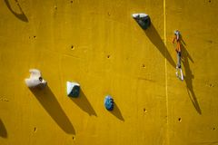 Yellow artificial climbing wall with holds royalty free stock photos