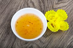 Sweet sauce. Yellow asian spicy sweet sauce on wood background Royalty Free Stock Photography