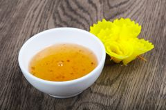 Sweet sauce. Yellow asian spicy sweet sauce on wood background Stock Photo