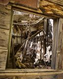 Looking Inside the Window of an Abandoned Home from the Wild West in Fall. Yellow aspen leaves liter the floor from the collapsed roof of an old abandoned home stock photography
