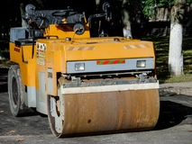 Yellow Asphalt Compactor or Road roller is ready to works for territory improvement. Human anthropogenic impact to nature Stock Image