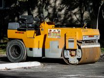Yellow Asphalt Compactor or Road roller is ready to works for territory improvement. Human anthropogenic impact to nature Royalty Free Stock Images