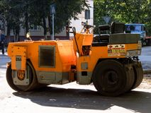 Yellow Asphalt Compactor or Road roller is ready to works for territory improvement. Human anthropogenic impact to nature Royalty Free Stock Photos