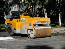 Yellow Asphalt Compactor or Road roller is ready to works for territory improvement. Human anthropogenic impact to nature Stock Photography