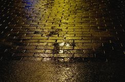 Yellow asphalt surface with puddles and paving slab. Raining weather. Royalty Free Stock Photos