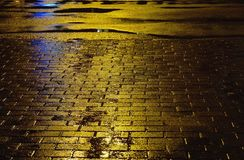Yellow asphalt surface with puddles and paving slab. Raining weather. Stock Photo