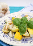Yellow aubergines. Some yellow baby aubergines with basil on a plate Royalty Free Stock Photos