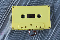 Yellow audio cassette on the gray wooden background. Stock Photography