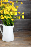 Yellow autumn flowers in a vase on the boards Stock Images