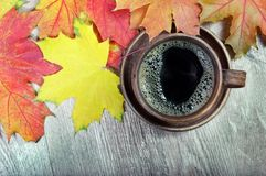 Yellow autumn leaf of maple and a cup of coffee. Top view royalty free stock photography