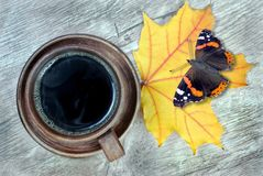 Yellow autumn leaf of maple and a cup of coffee. butterfly admiral on autumn maple leaf. Yellow autumn leaf of maple and a cup of coffee. top view. butterfly stock images