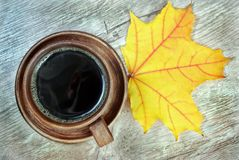 Yellow autumn leaf of maple and a cup of coffee. Top view royalty free stock image