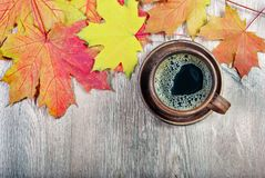 Yellow autumn leaf of maple and a cup of coffee. Top view stock image