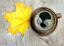 Yellow autumn leaf of maple and a cup of coffee. Top view royalty free stock photos