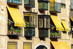 Yellow awnings on house wall. Yellow awnings over the windows. Sunny summer day Royalty Free Stock Photo