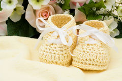 Yellow Baby Booties. A bouquet of flowers with a pair of baby booties, yellow baby booties Royalty Free Stock Image