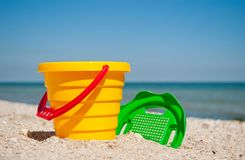 Yellow baby bucket with a red handle and a plastic green sieve left on a blue sea background sand summer sunny day, baby toys Stock Images