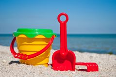 Yellow baby bucket with red handle, plastic red spatula and rake, and plastic green sieve, left on a background of blue sea sand s Royalty Free Stock Photo