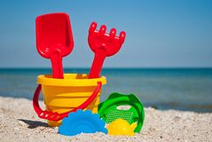 Yellow baby bucket with red handle, plastic red spatula and rake, and plastic green sieve, yellow sand form in the form of strawbe Royalty Free Stock Photos