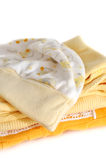 Yellow Baby Clothes. Pile of folded yellow baby clothes, on white stock photography
