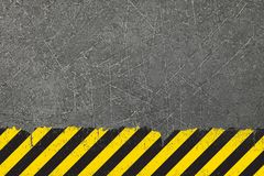 Yellow background with black grunge hazard sign. Old yellow weathered painted background with grunge black hazard sign stripes and copy space stock image